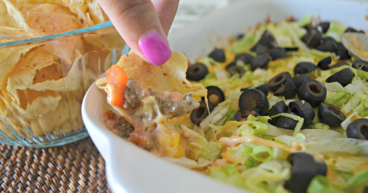 Scooping this baked taco dip with a corn chip