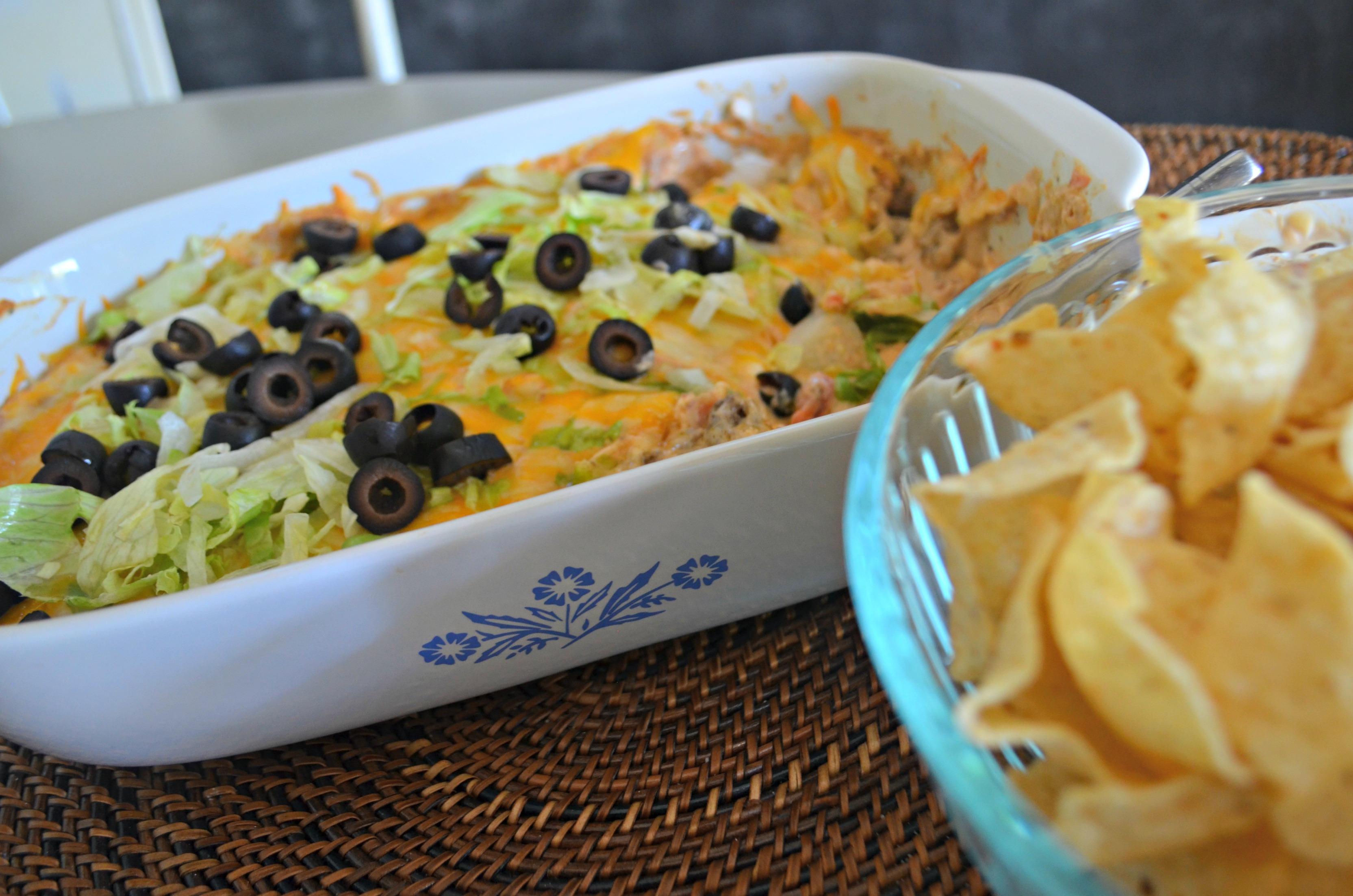 The baked taco dip in the baking dish with chips nearby.