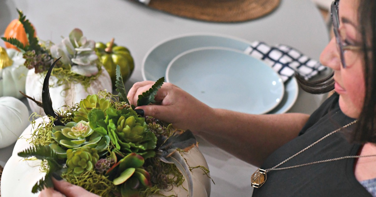 style your fall table with this DIY succulent centerpiece idea - here, Lina styling the pumpkin