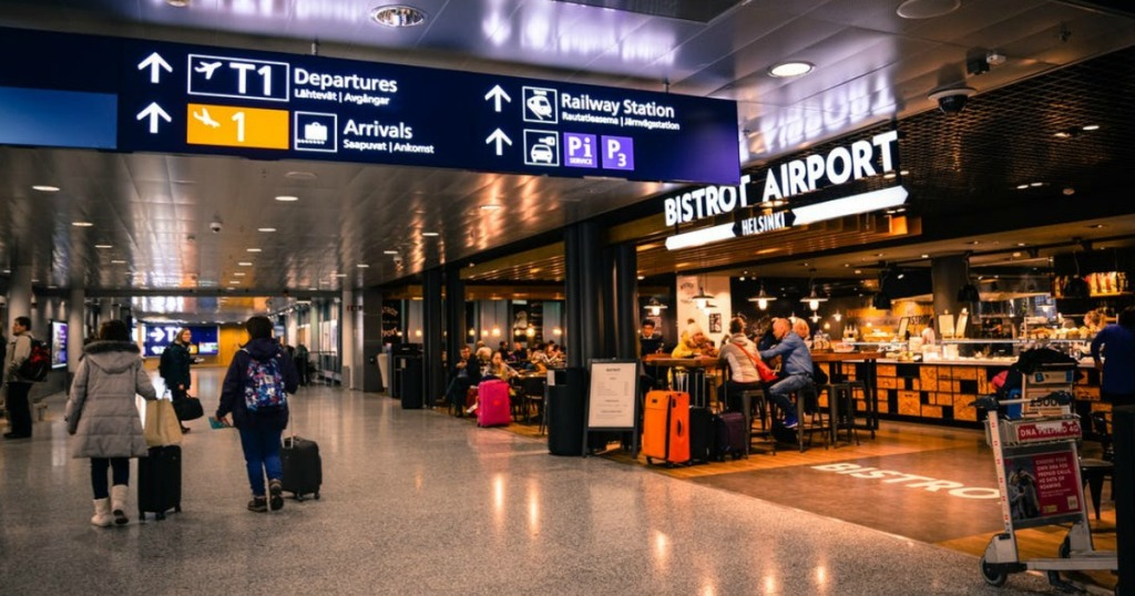 airport stores and hallway with various lights and signs for departures