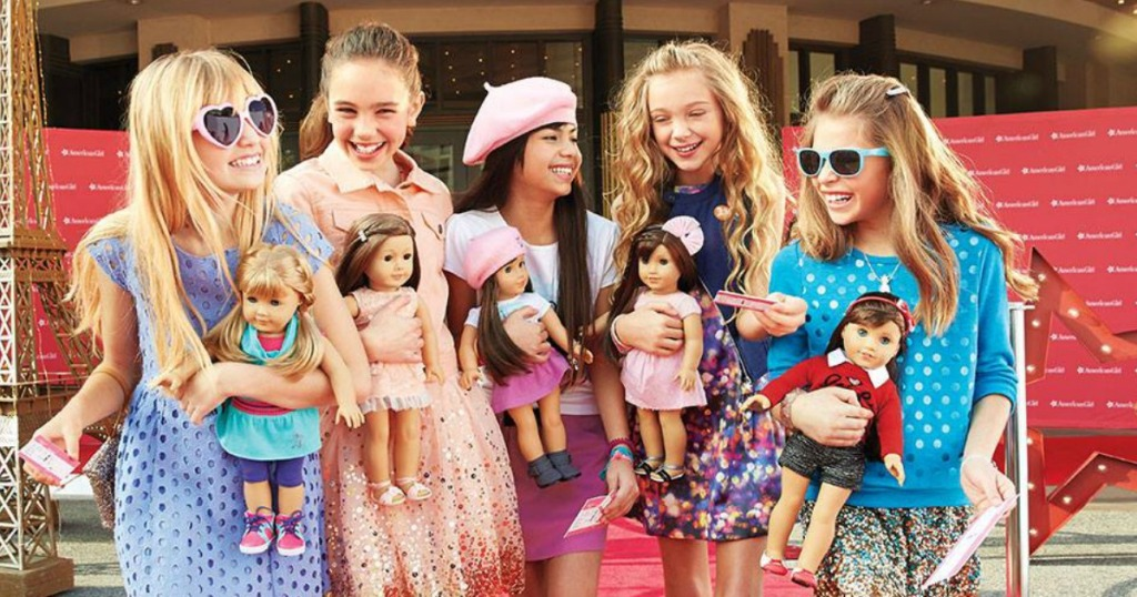 Little girls holding American girl dolls