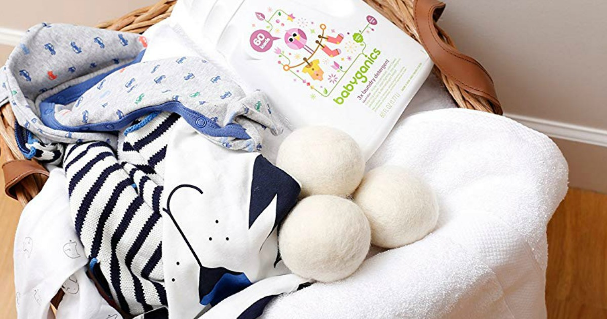 wool dryer balls with baby clothing in a basket