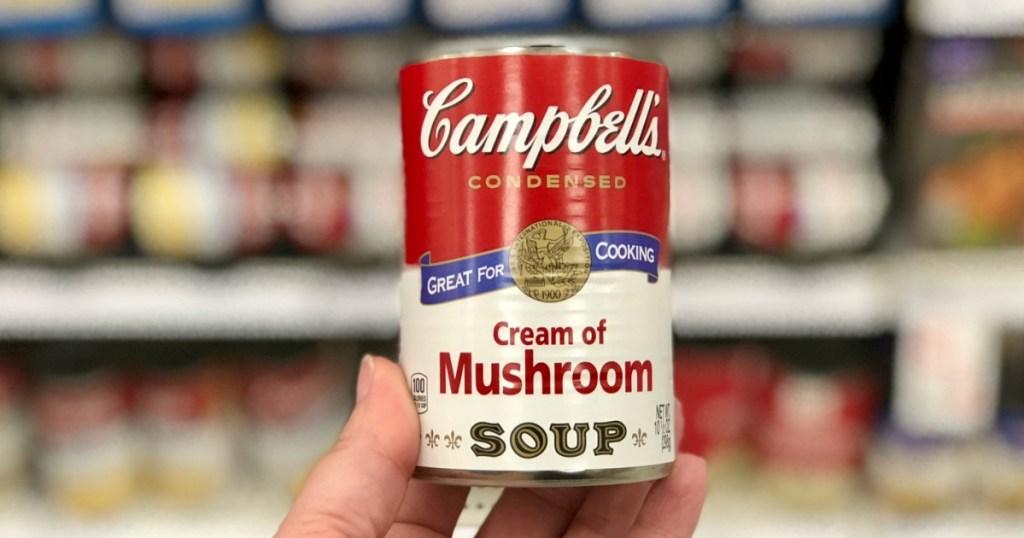 hand holding Campbell's Cream of Mushroom Soup