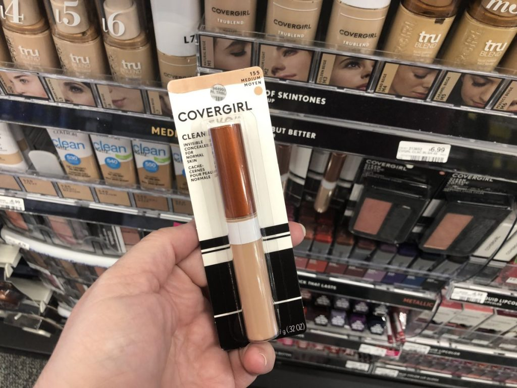 hand holding up a concealer makeup in store