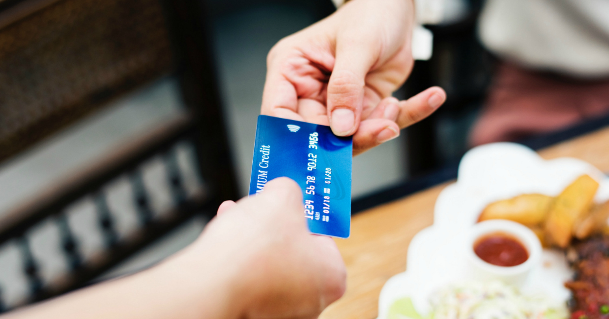 a new law provides free Credit Freezes and protection - One person handing a credit card to another