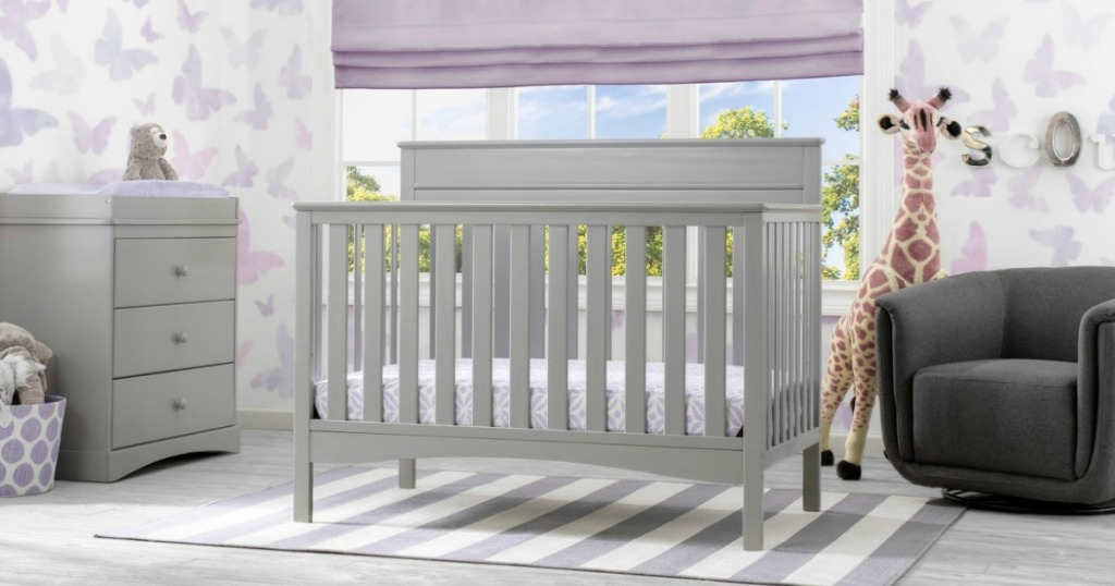 grey crib in front of window