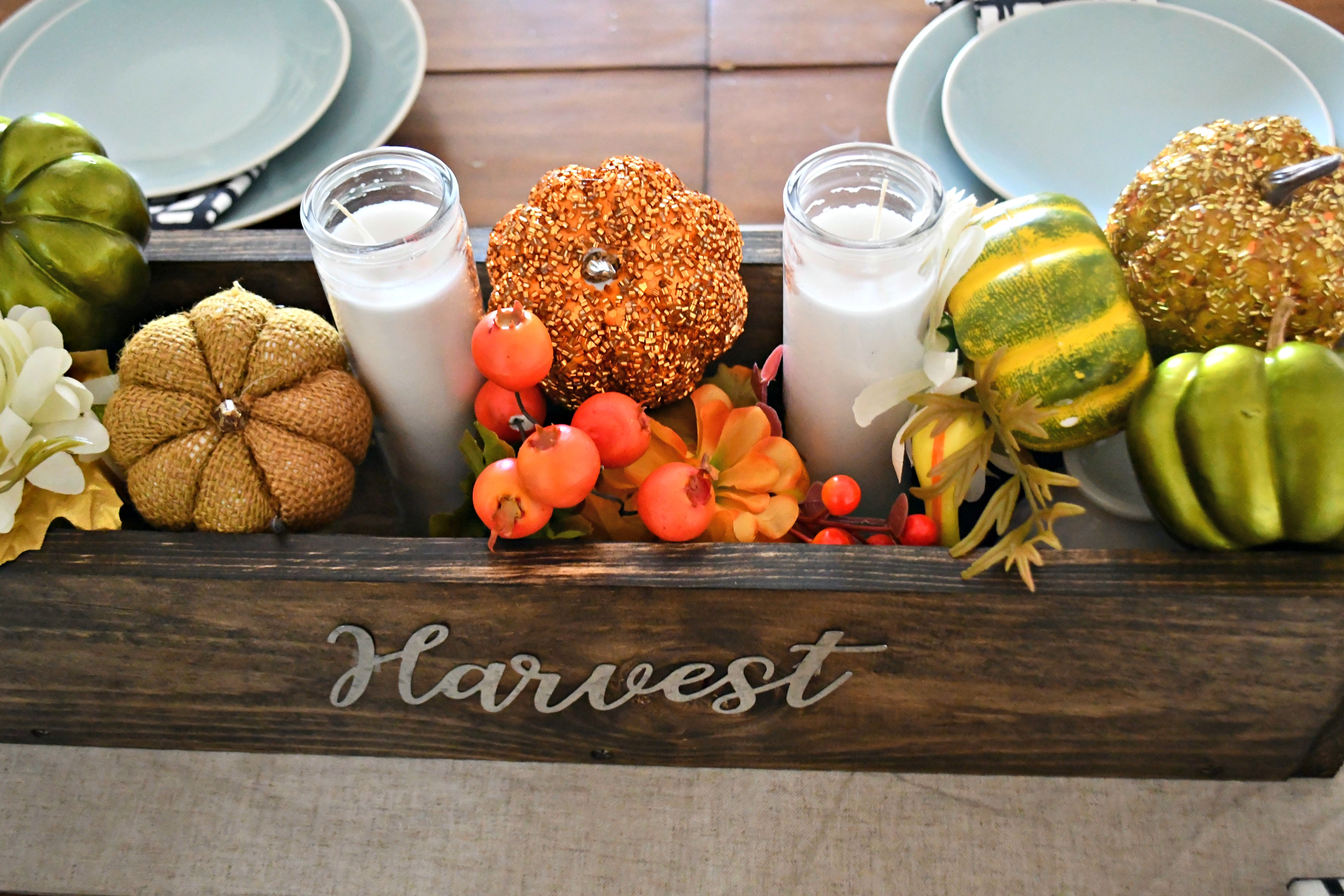 "dollar tree fall centerpiece - this is a side view of the wooden box with pumpkins, greenery, and ""harvest"" lettering"