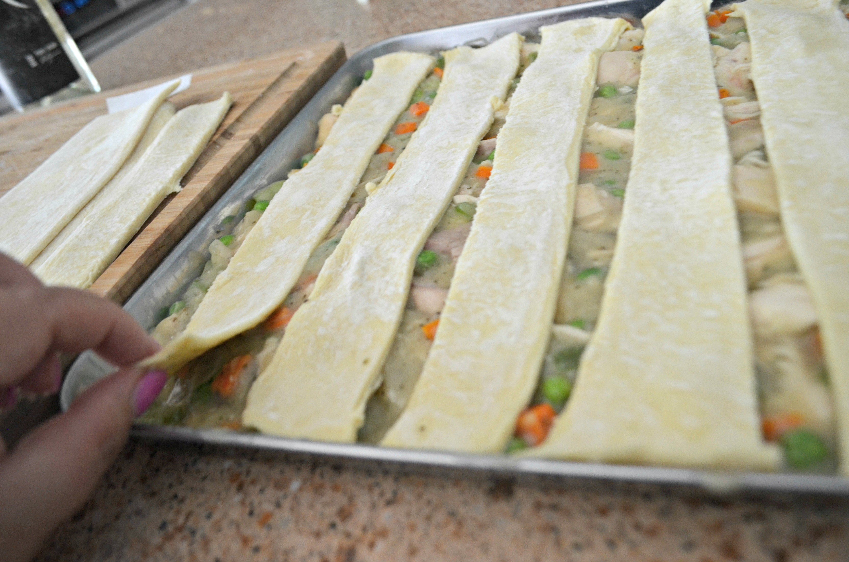 Sheet Pan Chicken Pot Pie -layering dough on top of the mixture in the pan