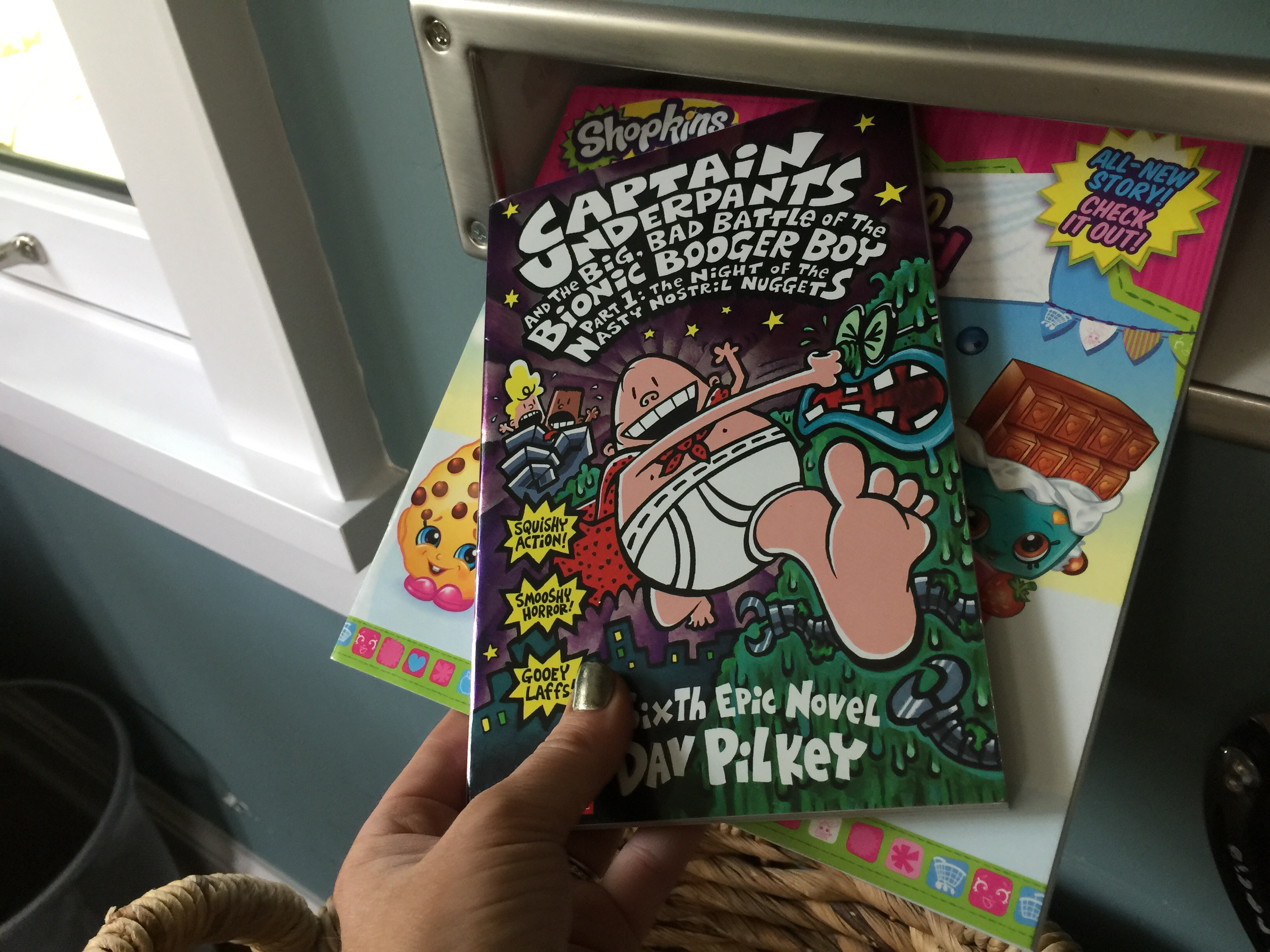 hand holding a Captain Underpants and Shopkins book