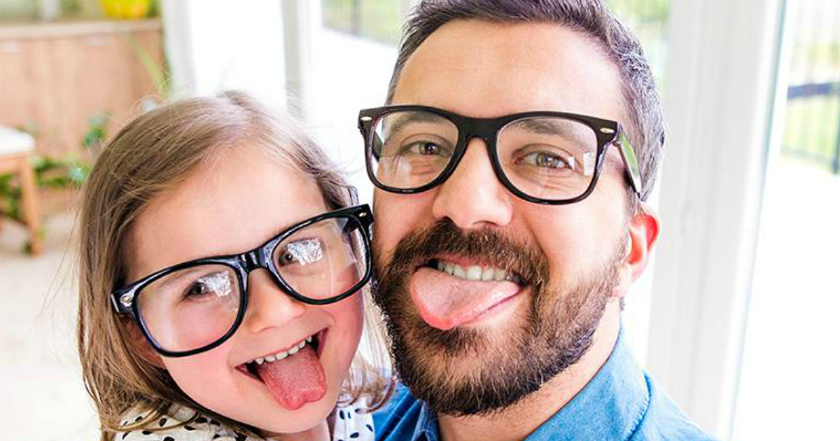 a dad and daughter making a funny face at the camera