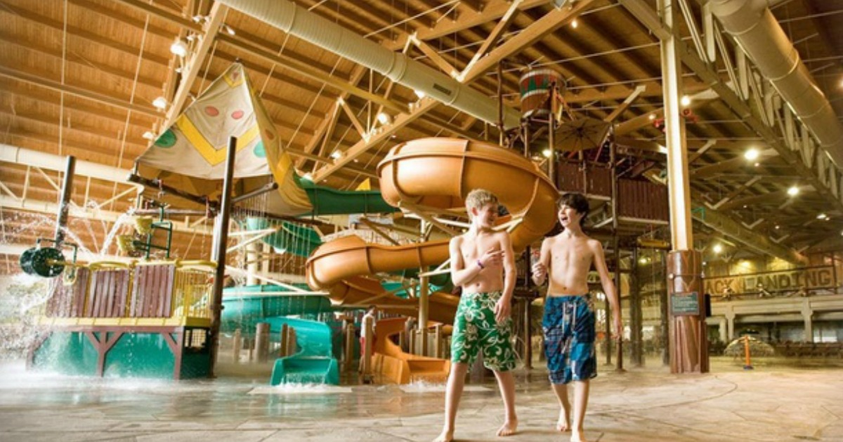 two boys in swim trunks walking in front of indoor water slides
