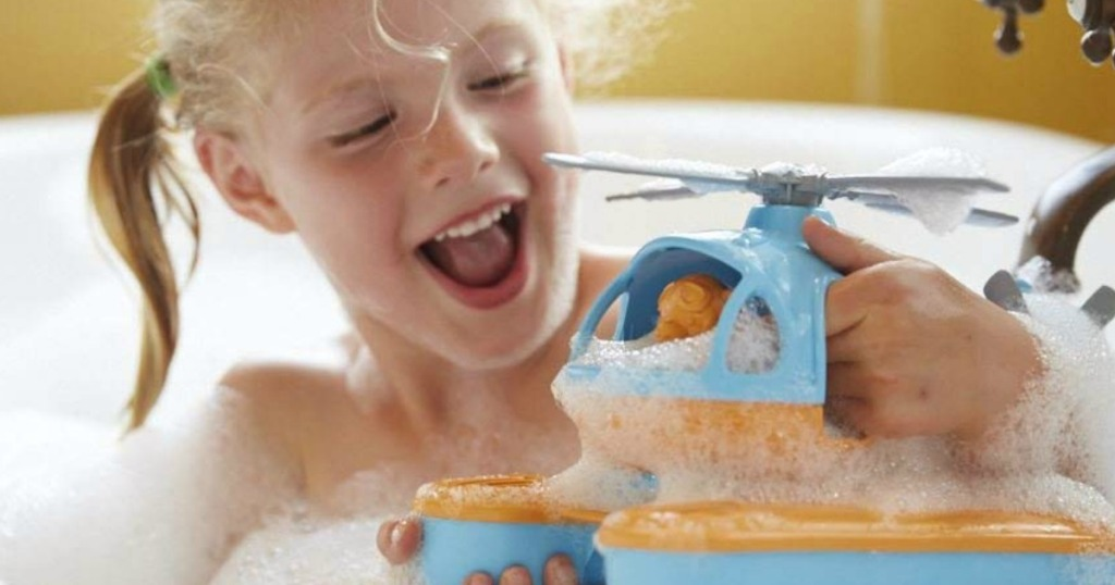 little girl holding a green toys orange sea copter in a bath tub