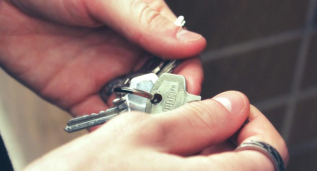hands holding set of silver metal keys