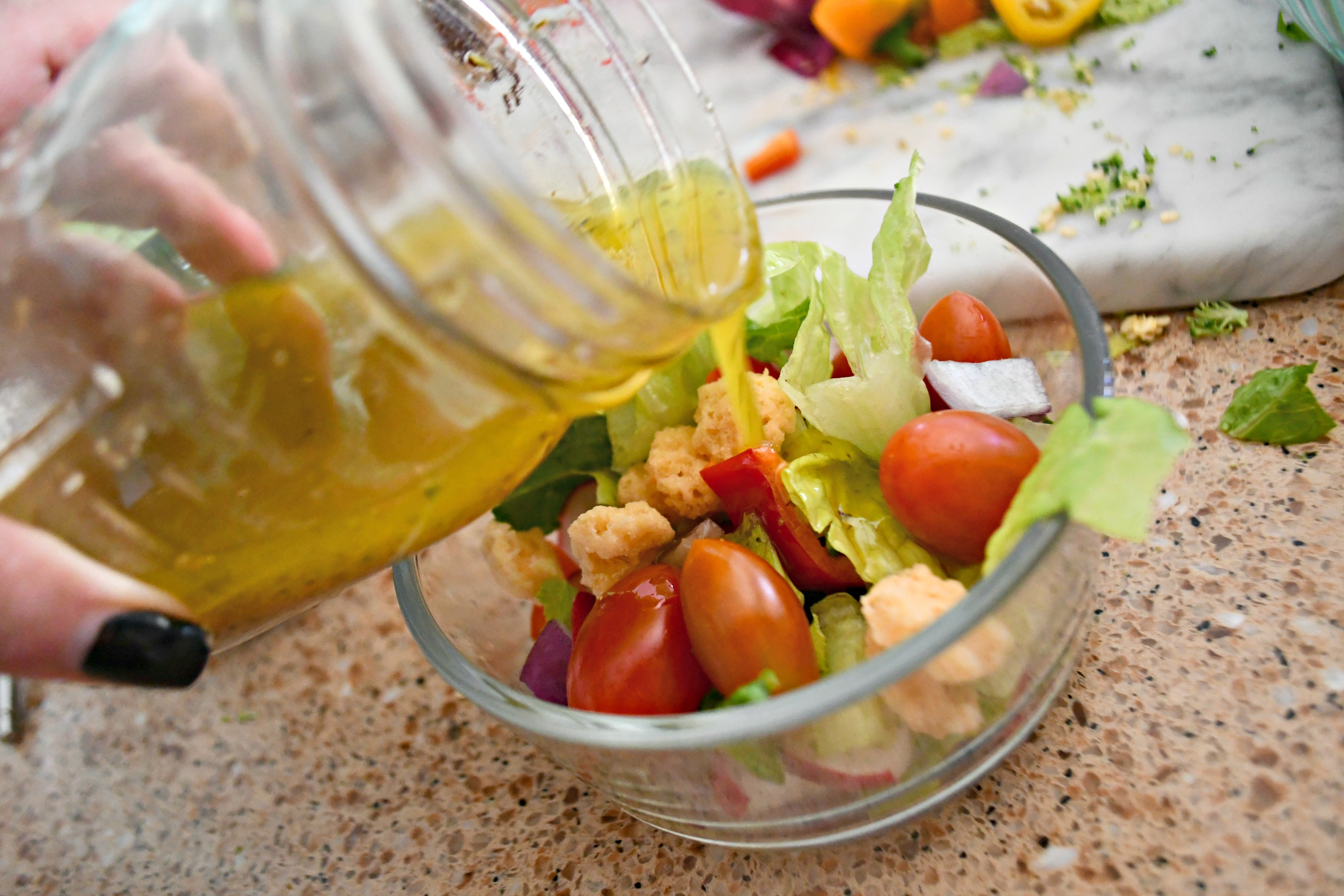 Pouring my favorite salad dressing over my Weekly Sunday Salad Prep