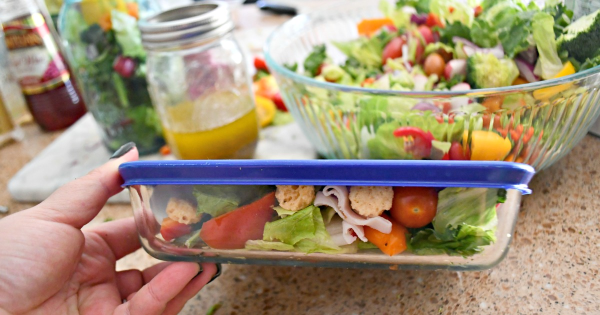 packing a salad in a clear glass container