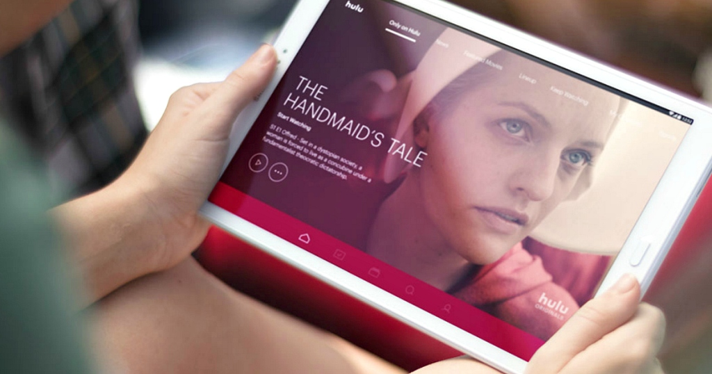 woman holding a white tablet with hulu app open showing handmaid's tale