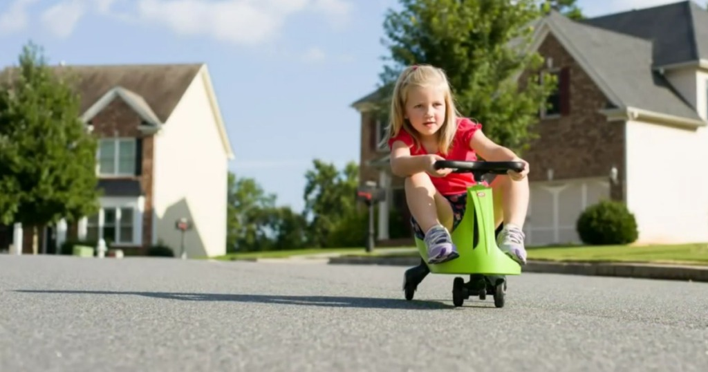 girl riding swing car ride-on toy on road