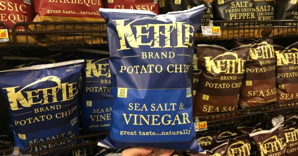 hand holding kettle brand sea salt & vinegar chips in front of chip display