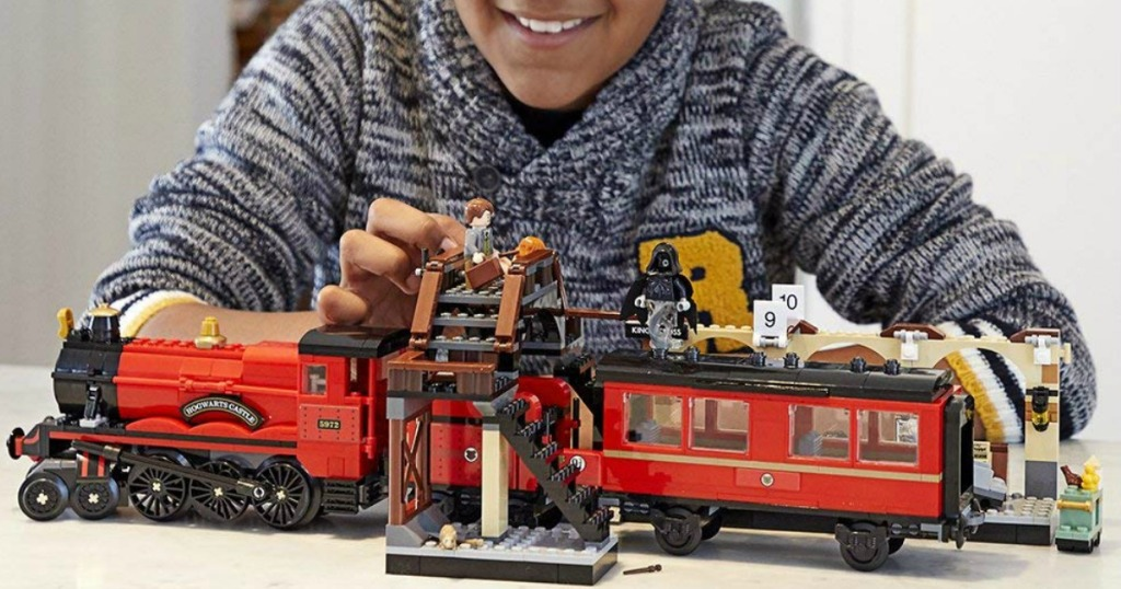 kid playing with a LEGO train set