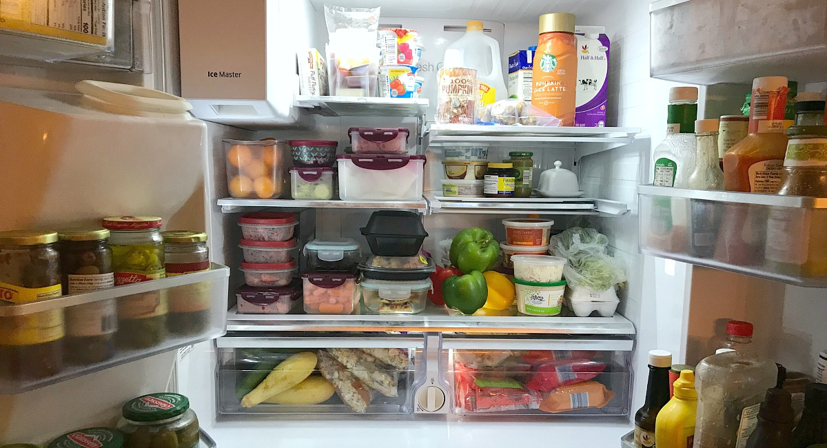 amber's organized meal plans and grocery shops — fridge opened showing pre portioned tupperware containers