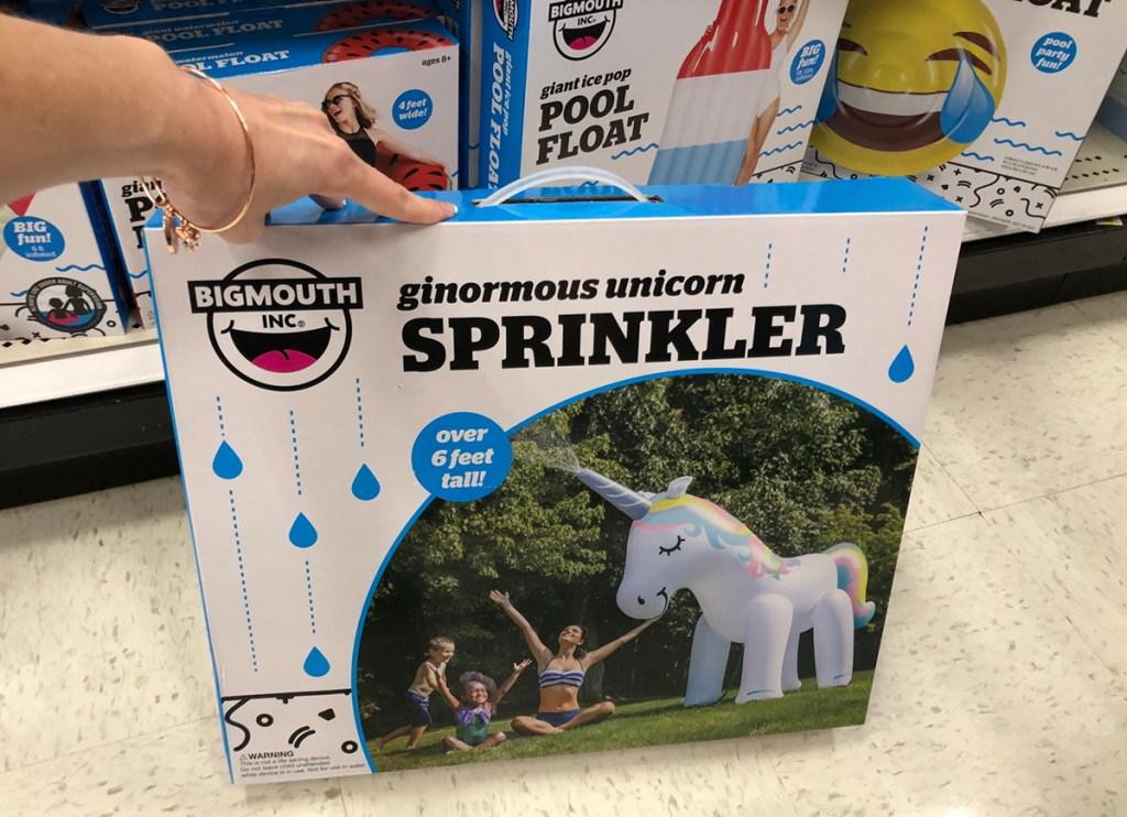 hand holding big mouth unicorn yard sprinkler