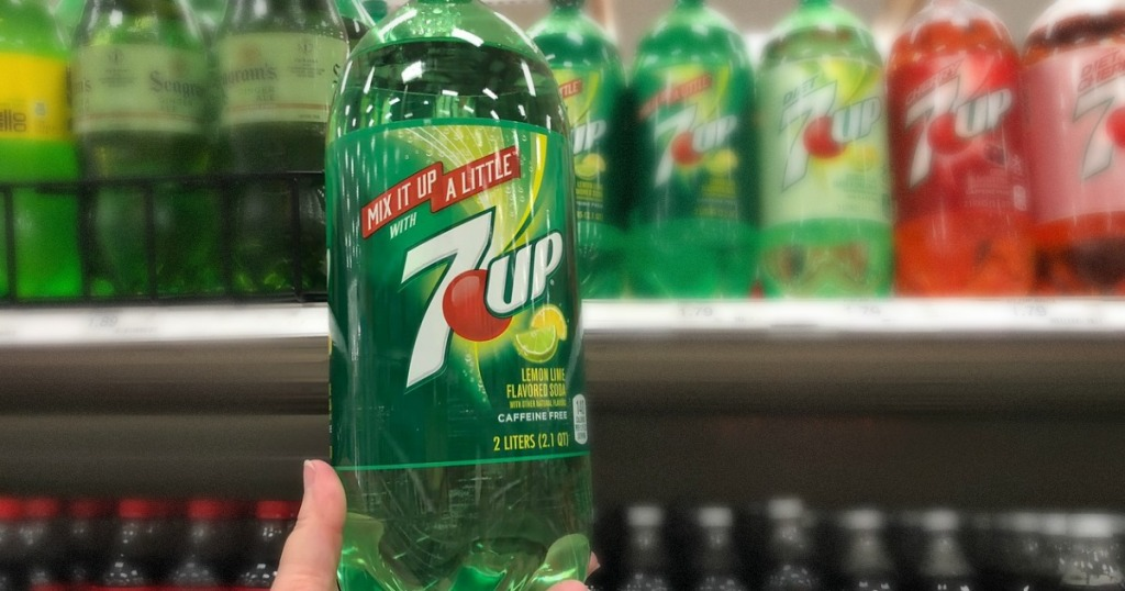 hand holding bottle of soda in front of shelf