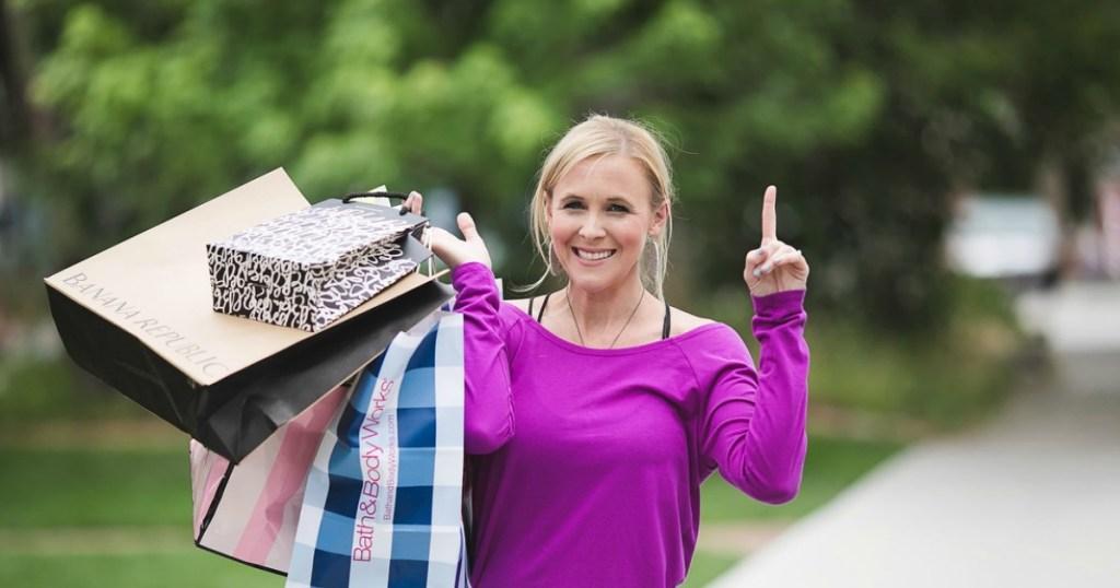 woman wearing pink shirt with shopping bags