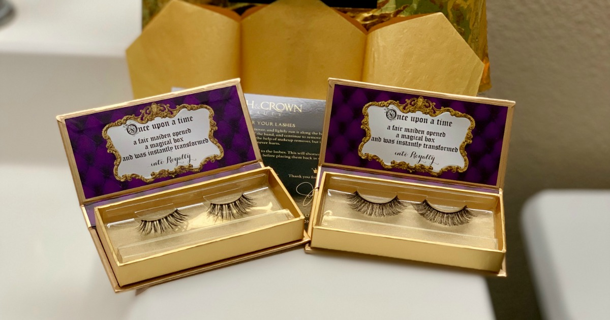 two sets of black false lashes sitting in gold and purple boxes on white countertop