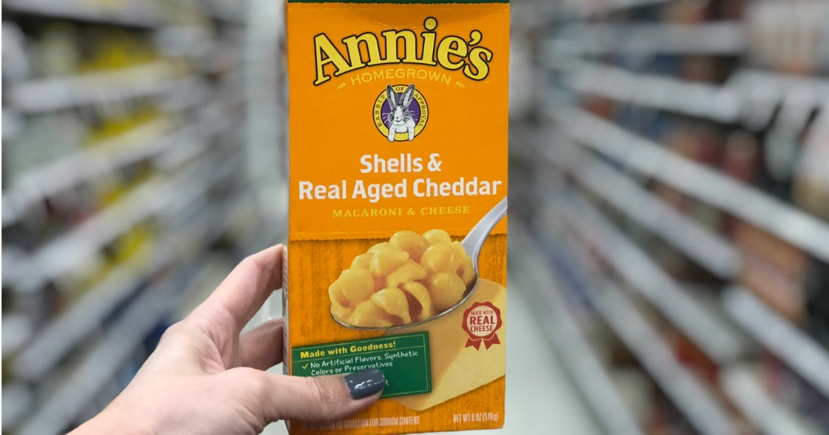 hand holding a box of annies shells and cheese