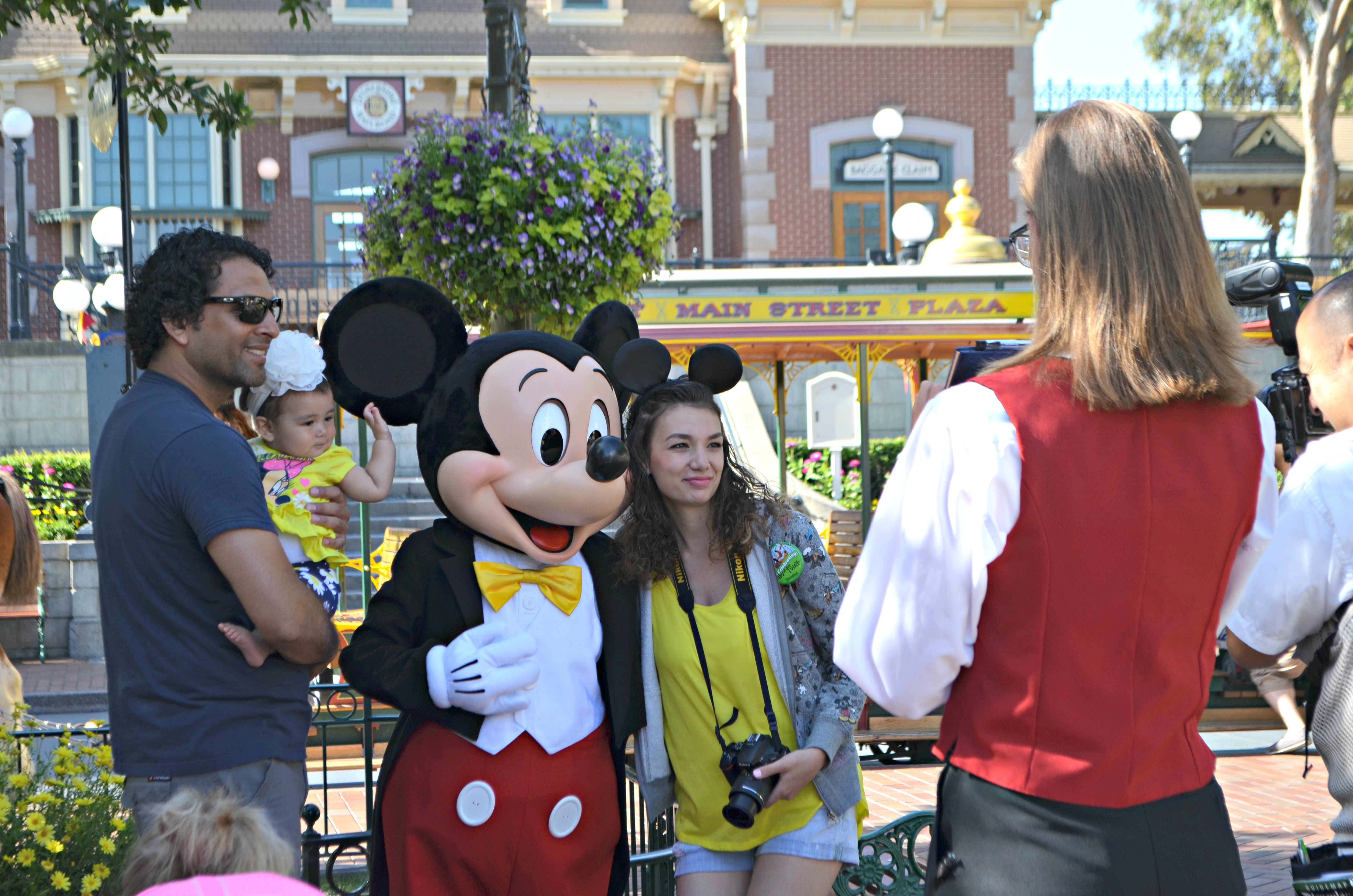 disney world ticket prices are based on peak dates – a young family posing with Mickey Mouse