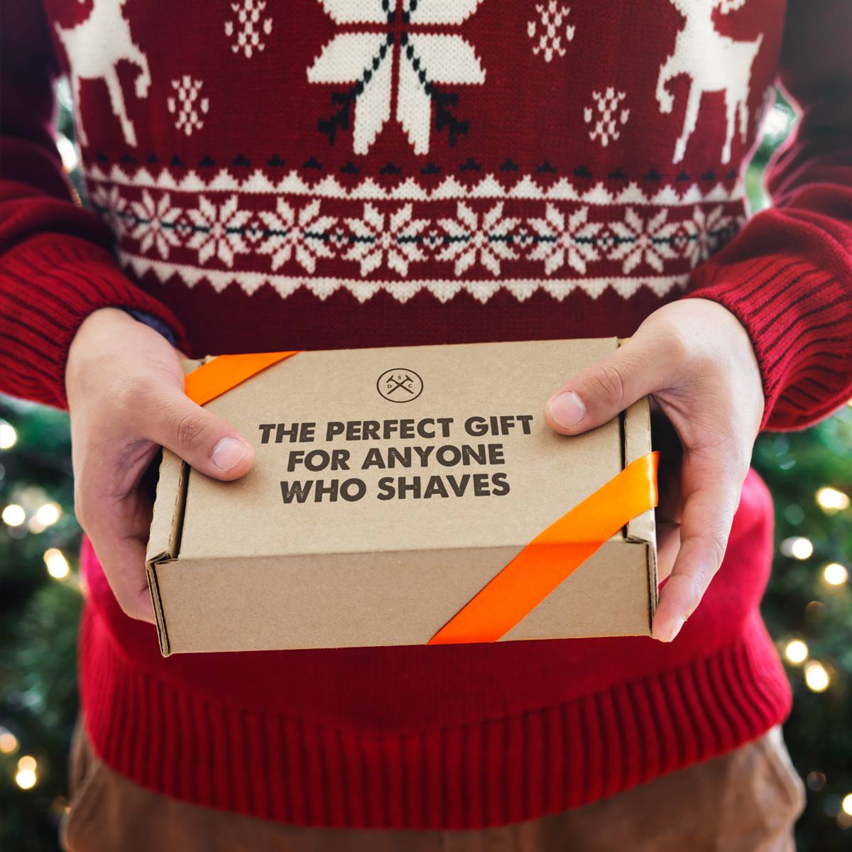 Get a Dollar Shave Club starter kit for just $5 – someone with a Christmas sweater holding the box