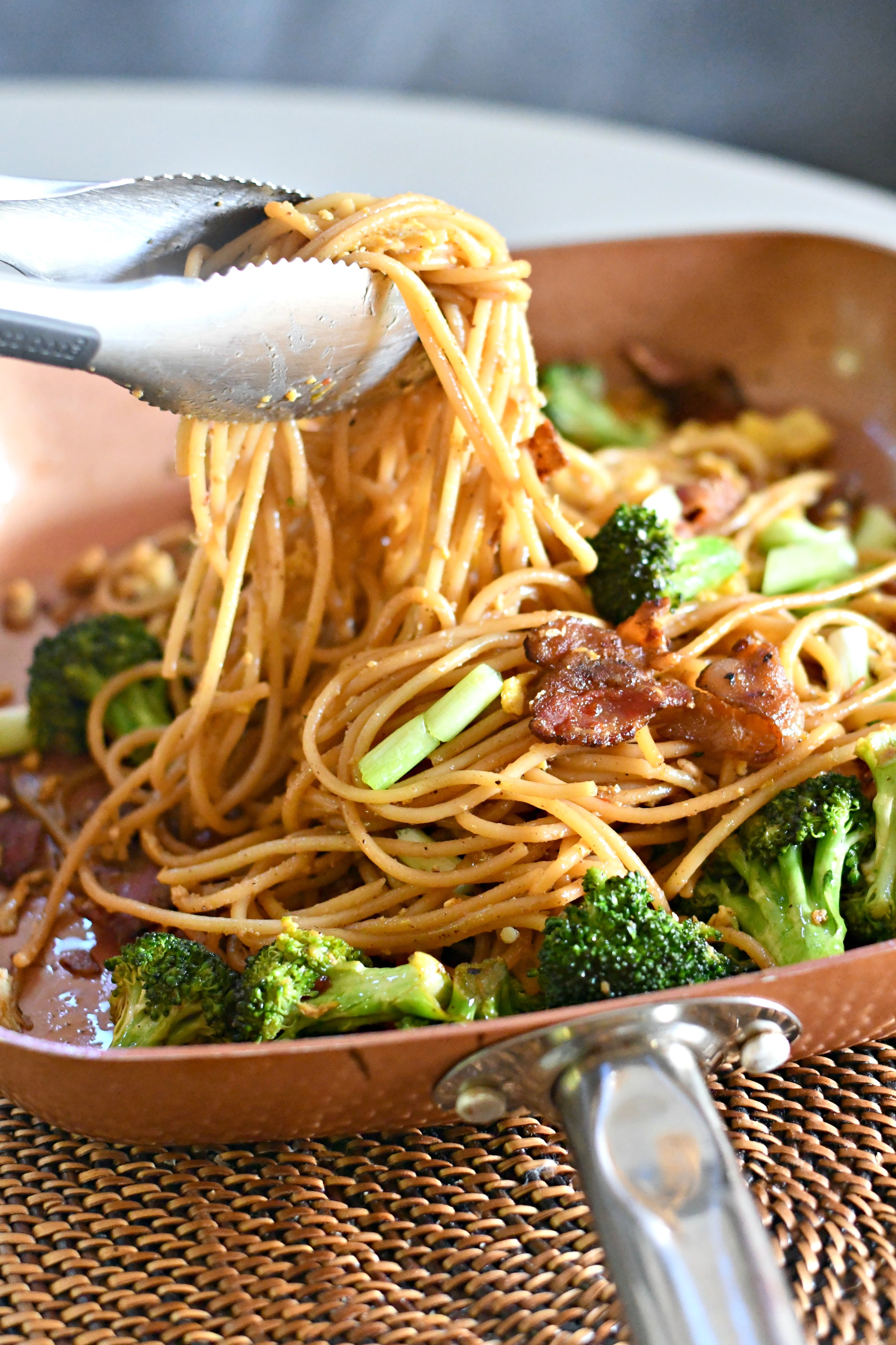 Cravings: Hungry for More Cookbook by Chrissy Teigen – noodle dish in a copper pan being served with tongs