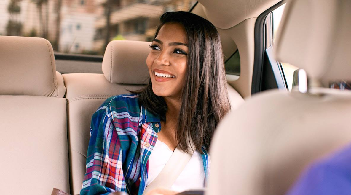Uber and Lyft are offering free and reduced-rate rides election day – A young woman in the back seat of a car