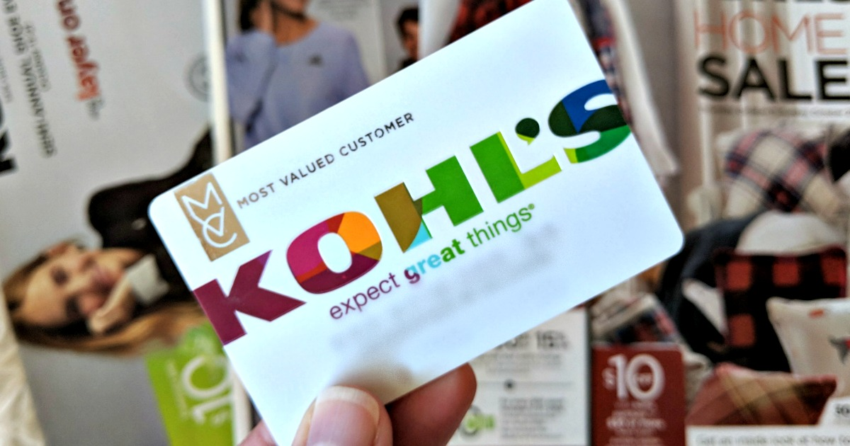 Kohl's credit card in-hand in front of Kohl's ad