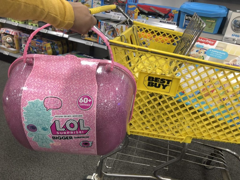 hand holding pink toy in front of shopping cart