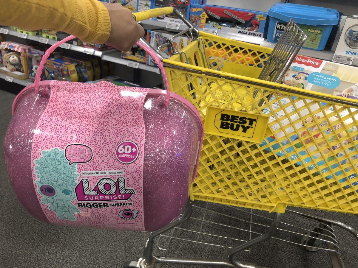 LOL Surprise Bigger Surprise held in hand pushing Best Buy cart