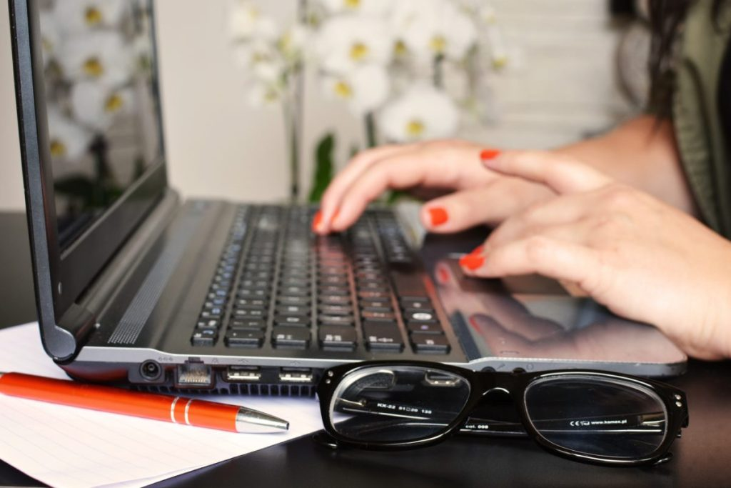 Glasses next to computer with woman typing