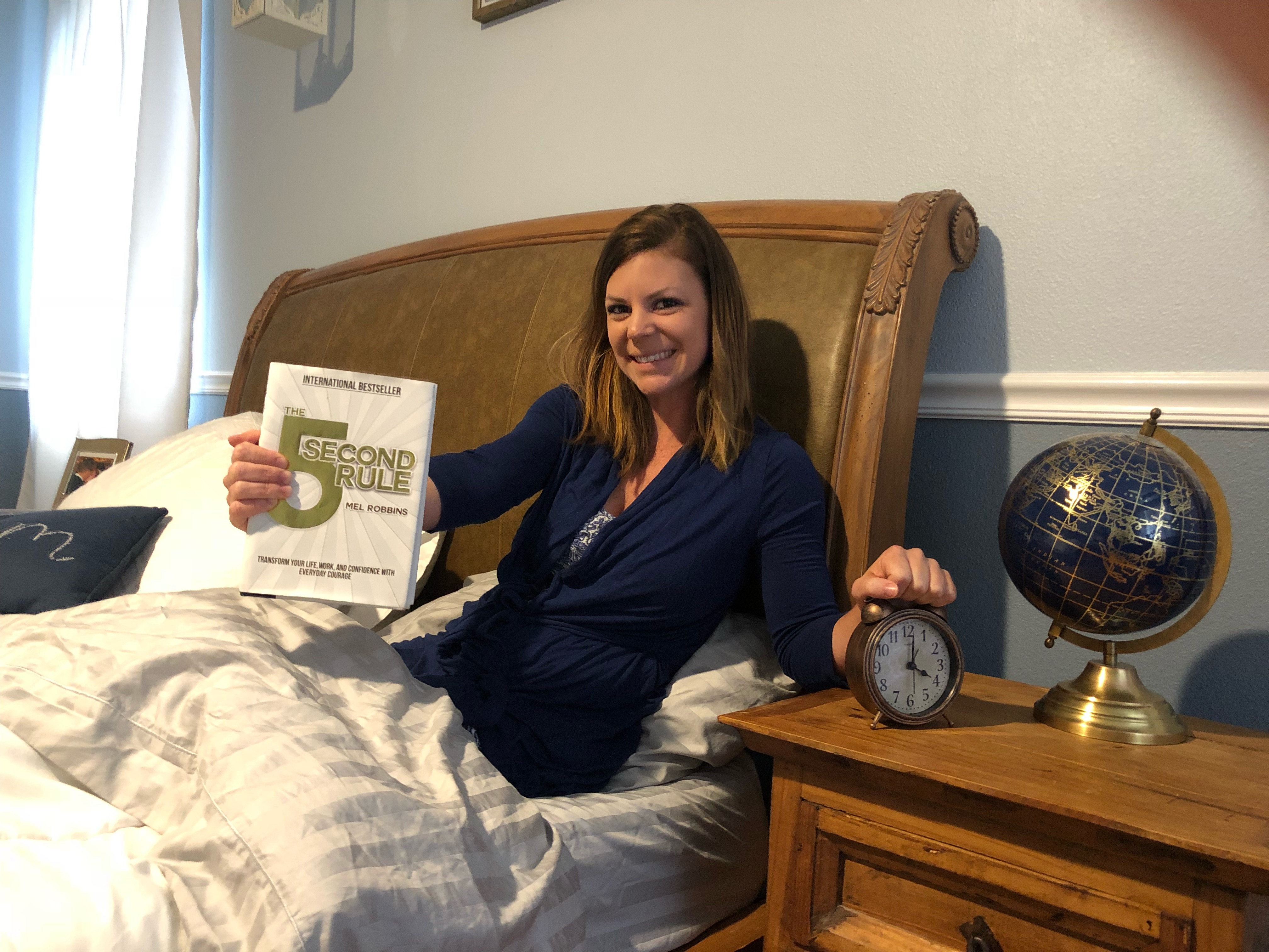 changed life 5 seconds – Erica holding the 5-second rule book and her alarm clock, smiling
