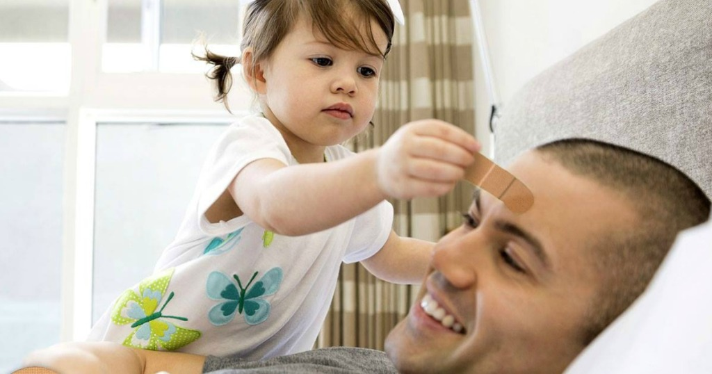 little girl playing with band-aid on dad's forehead