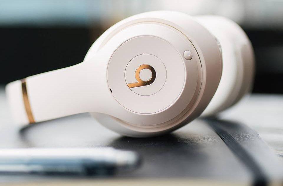pair of white headphones on desk