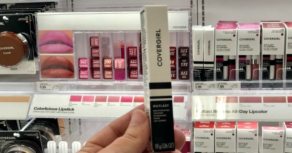 woman holding up covergirl lip stick at target