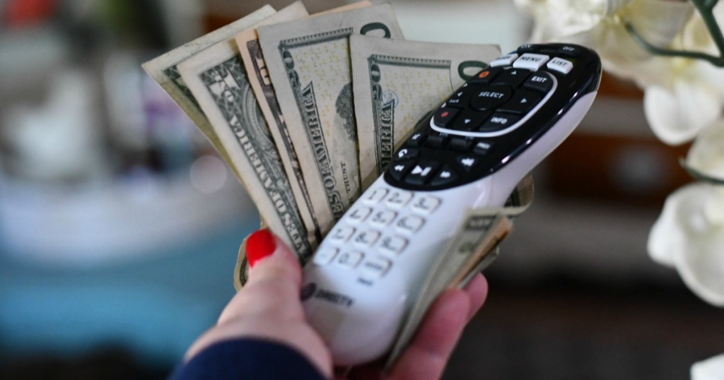 Woman holding DirecTV Remote Control and cash