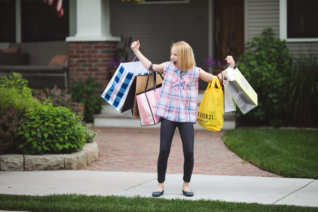 girl with tons of shopping bags outside