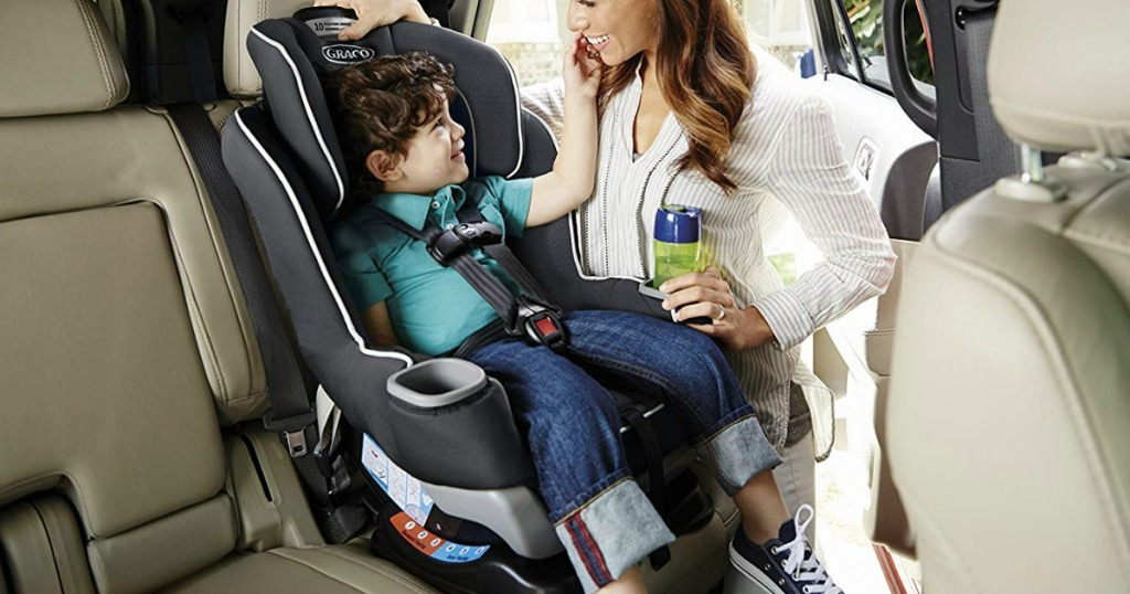 mom standing next to child in carseat in car