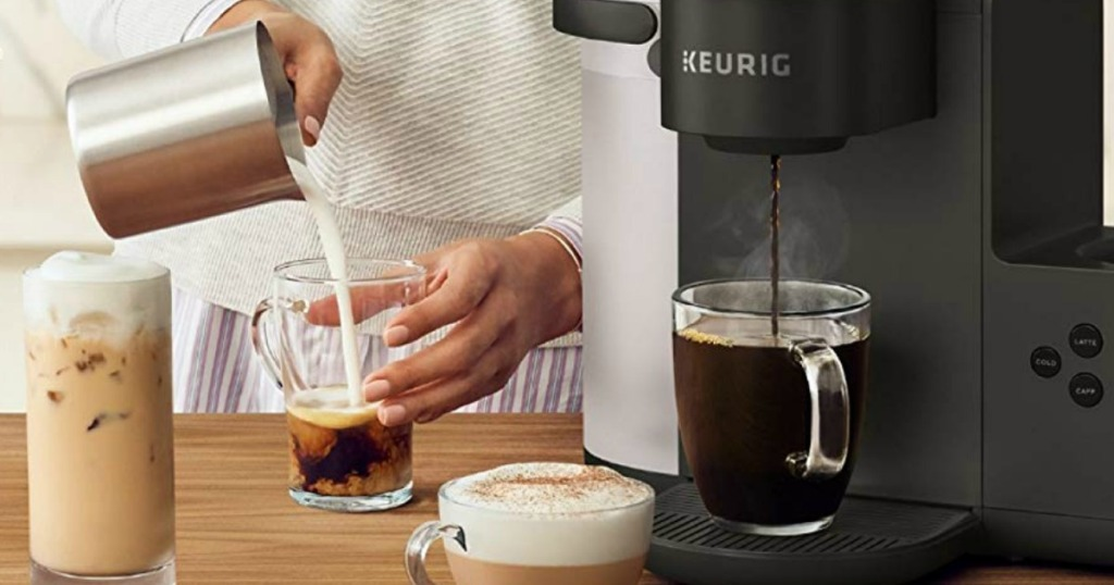 person pouring foam into a coffee drink next to a coffeemaker