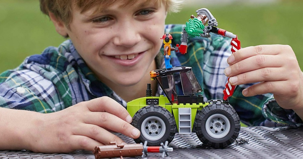 child playing with LEGO tractor