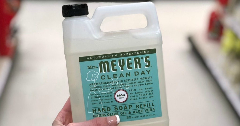 hand holding mrs meyers soap refill with blurred background