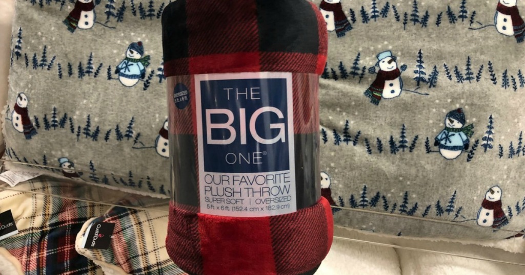 the big one plaid plush throw in-store with plush throws in background