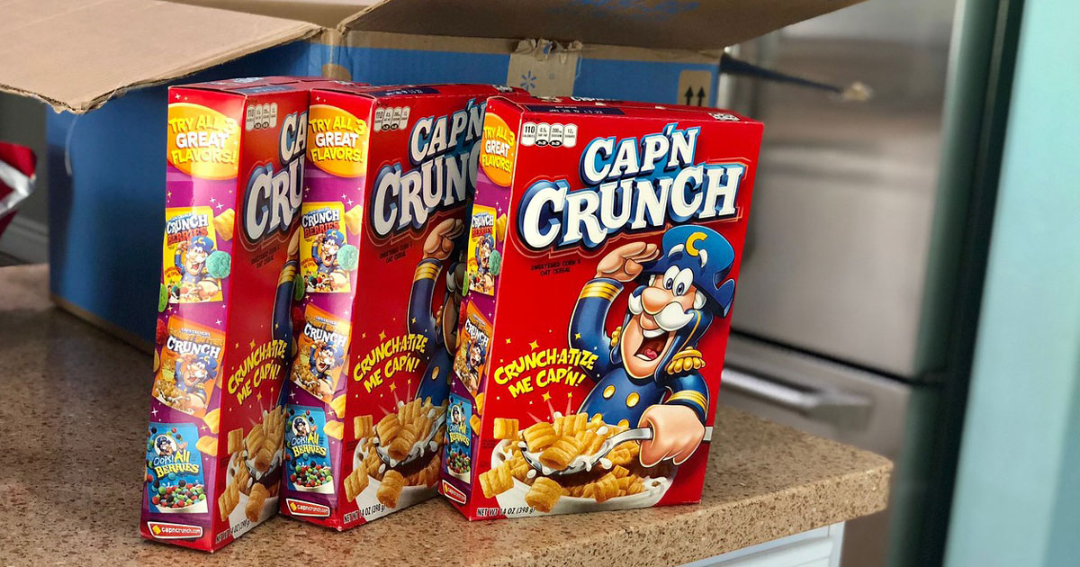 three boxes of capn crunch cereal on a counter in a kitchen