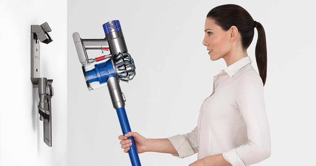 woman putting dyson v6 fluffy on wall charger